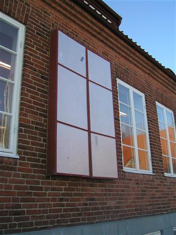 En tætlukkende kasse spændes fast omkring vindueskarmen indefra, så vinduet kan hægtes af og restaureres.